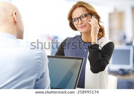Portrait of mature business woman using mobile white sitting at office with businessman. Teamwork. - stock photo
