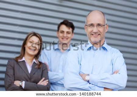 Portrait of mature businessman and team standing with arms crossed against shutter - stock photo