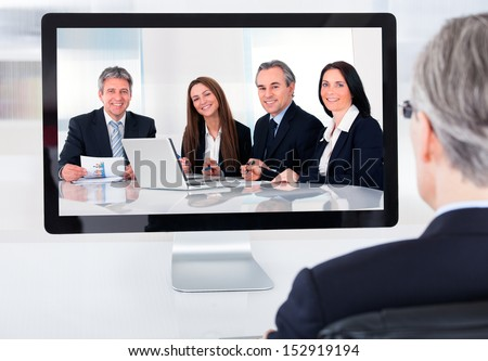 Portrait of mature businessman attending video conference - stock photo