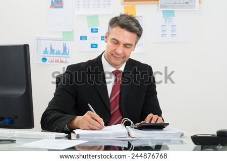 Portrait Of Mature Businessman Calculating Finance At Office Desk - stock photo