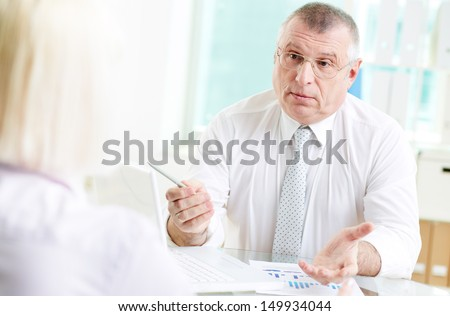 Portrait of mature businessman looking at his partner while talking to her in office - stock photo
