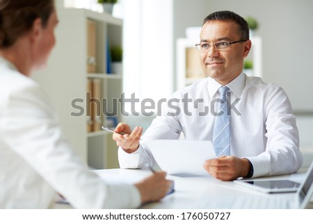 Portrait of mature businessman looking at his secretary while speaking to her
