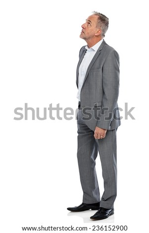 Portrait of mature businessman looking up at copyspace on white background