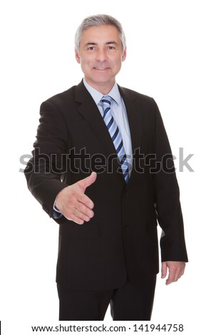 Portrait Of Mature Businessman Offering Handshake Over White Background
