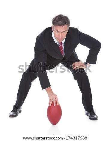 Portrait Of Mature Businessman Ready To Play American Football - stock photo