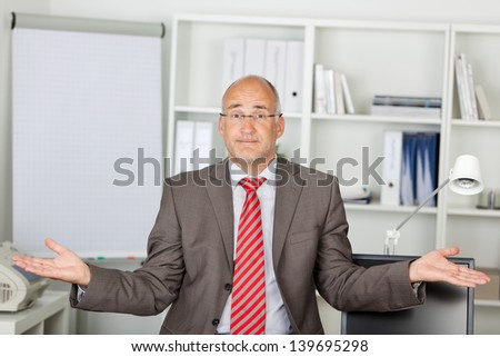 Portrait of mature businessman shrugging shoulders in office - stock photo