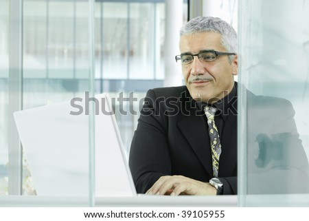 Portrait of mature businessman sitting at desk in modern office, using laptop computer.