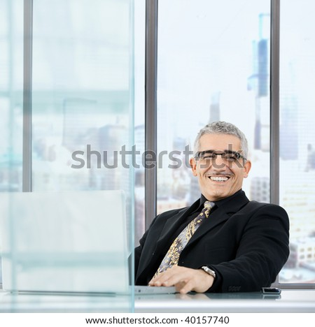 Portrait of mature businessman sitting at desk in orporate office, using laptop computer, smiling.