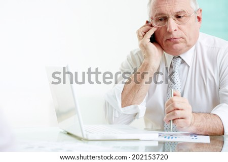Portrait of mature businessman speaking on the phone in office - stock photo