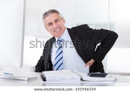 Portrait Of Mature Businessman Suffering From Back Pain - stock photo