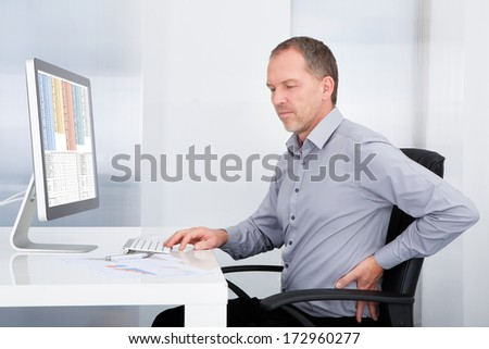 Portrait Of Mature Businessman Suffering From Back Pain
