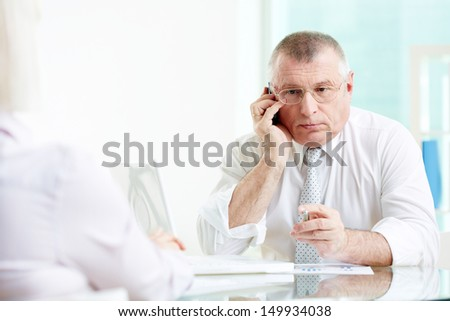 Portrait of mature businessman talking on the phone in office - stock photo