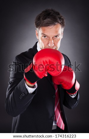 Portrait Of Mature Businessman Wearing Red Boxing Gloves