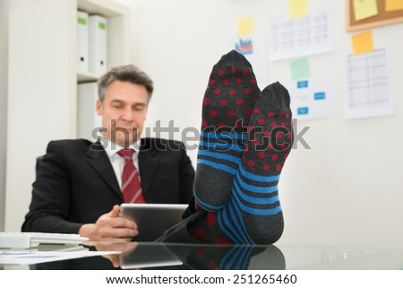 Portrait Of Mature Businessman With Socks In His Feet Using Digital Tablet At Office - stock photo