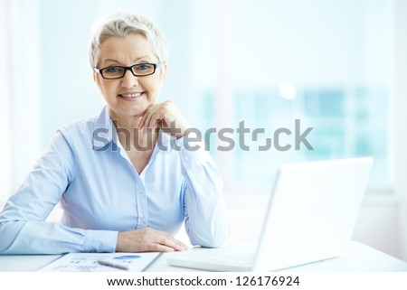 Portrait of mature businesswoman in eyeglasses looking at camera - stock photo