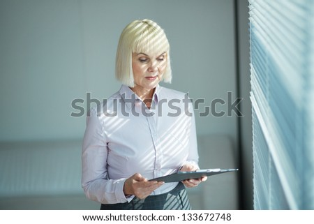 Portrait of mature businesswoman looking at document in office - stock photo