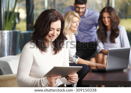 Portrait of mature businesswoman sitting at office and checking e-mails on digital tablet while her colleagues working at background in front of laptop. Teamwork at office.  - stock photo
