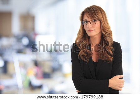 Portrait of mature businesswoman standing in her office. - stock photo