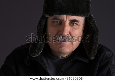 Portrait of mature Caucasian man in fur-cap against dark background