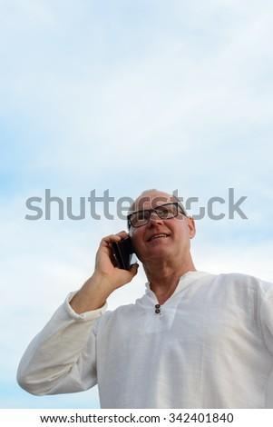 Portrait of mature Caucasian man outdoors talking on phone