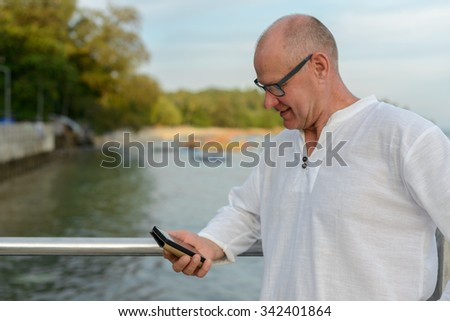 Portrait of mature Caucasian man outdoors using mobile phone