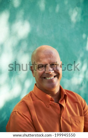 Portrait of mature caucasian man with orange shirt sitting in park and looking at camera with happy expression - stock photo