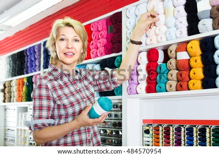portrait of mature cheerful female customer standing next to shelf with knitting yarn in shop