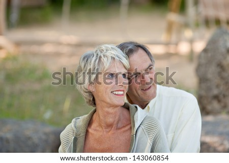 Portrait of mature couple looking over the nature background - stock photo