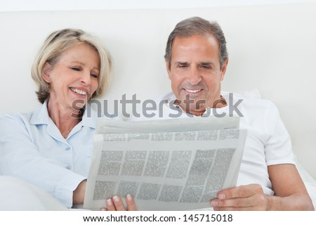 Portrait Of Mature Couple Reading Newspaper Together At Home - stock photo