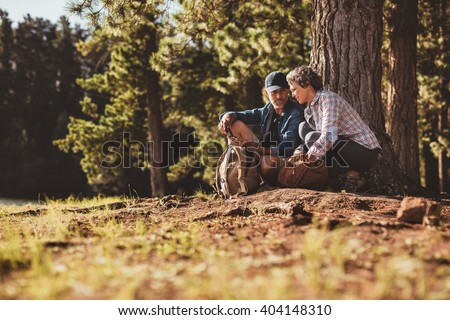 Portrait of mature couple sitting together in nature with a compass. Senior man and woman using compass for directions in forest. - stock photo