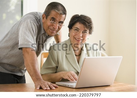 Portrait of mature couple with laptop