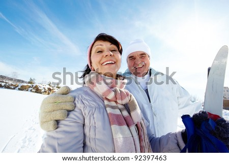 Portrait of mature couple with skis outside