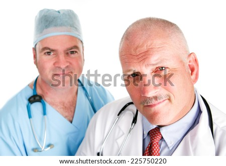 Portrait of mature doctor and younger surgeon isolated on white.   - stock photo
