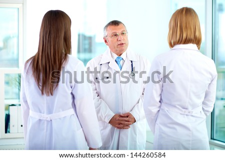 Portrait of mature doctor talking to one of two young clinicians in hospital - stock photo