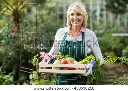 Portrait of mature female gardener holding vegetables crate at greenhouse