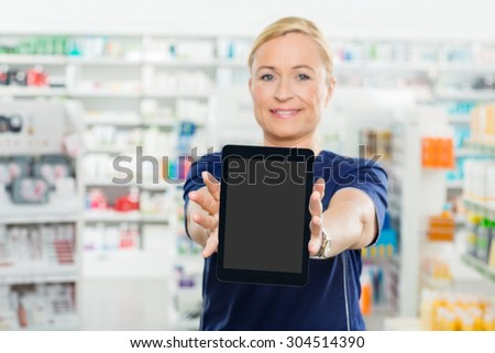 Portrait of mature female pharmacist showing digital tablet with blank screen in pharmacy - stock photo