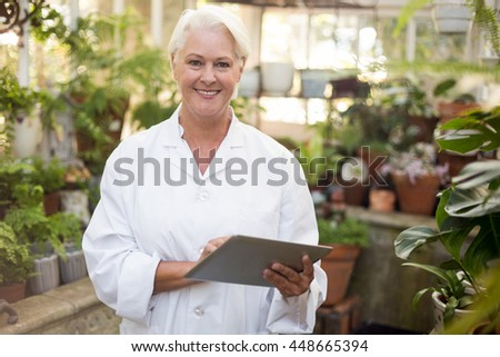 Portrait of mature female scientist smiling while using digital tablet at greenhouse