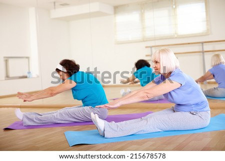 Portrait of mature females doing stretching exercise in sport gym  - stock photo