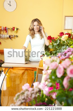 Portrait of mature flower shop owner using her telephone and laptop to take delivery service for her store.  - stock photo