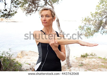 Portrait of mature healthy woman stretching her arms, exercising in coastal nature with trees, rocks and the sea, outdoors. Wellness and fitness lifestyle, senior woman athlete discipline and effort. - stock photo