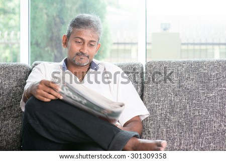 Portrait of mature Indian man reading on newspaper, sitting on sofa at home. Asian male relax on couch in house with interior. - stock photo
