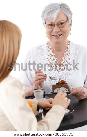 Portrait of mature lady sitting at coffee table, eating cake, smiling.?