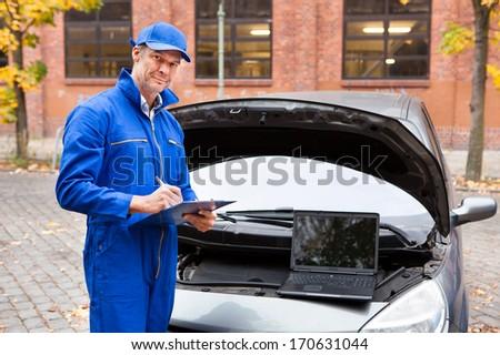 Portrait Of Mature Male Automotive Mechanic Writing On Clipboard - stock photo