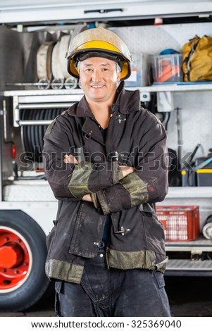 Portrait of mature male firefighter standing arms crossed against firetruck at station - stock photo