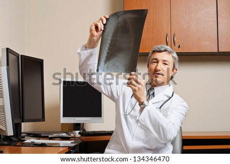 Portrait of mature male radiologist holding shoulder x-ray while sitting by desk at clinic - stock photo
