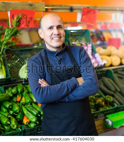Portrait of mature male seller posing at market with seasonal veggies and smiling