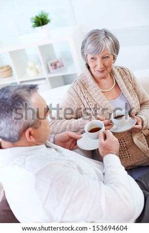 Portrait of mature man and his wife drinking tea and interacting - stock photo