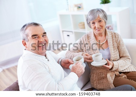 Portrait of mature man and his wife drinking tea at home - stock photo