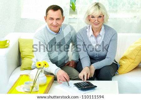 Portrait of mature man and his wife looking at camera while making financial revision at home - stock photo