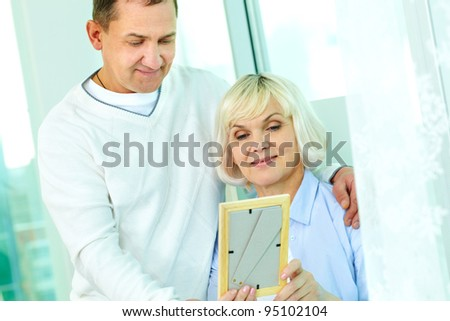 Portrait of mature man and his wife looking at photograph in frame - stock photo